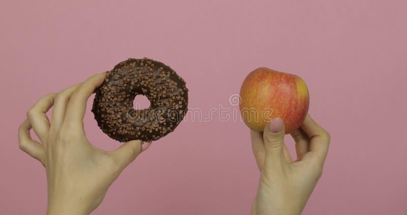 Handen houdt donut en appel Keuze tegen appel Gezonde of junkfood stock afbeelding