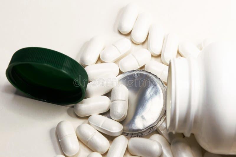 在白色背景和白色药片驱散的特写镜头瓶子 图库摄影