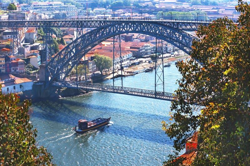 """€ de Porto, Portugal """"2 de maio de 2019: Vista panorâmica pitoresca da ponte de Luis I do metal, do rio de Douro com barco e de  fotos de stock royalty free"""