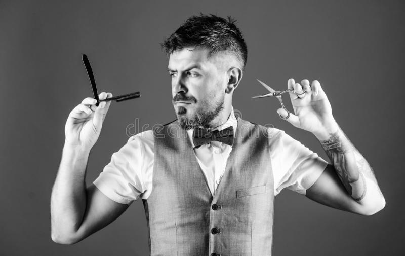 剪或刮 复古理发店带剃须刀和剪刀的蓄须男 理发师手持复古理发工具 库存图片