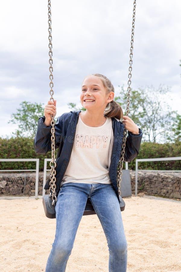 Mała dziewczynka bawić się w parku w zielonym tle zdjęcie stock