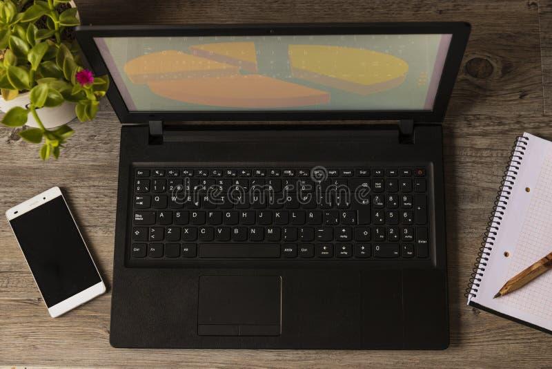 Tabela de madeira da planta do caderno do telefone do computador fotos de stock