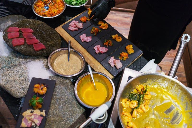 Vista superior de los aperitivos cocinados para los clientes Camarón, atún y ensaladas en la mesa Comida imagen de archivo