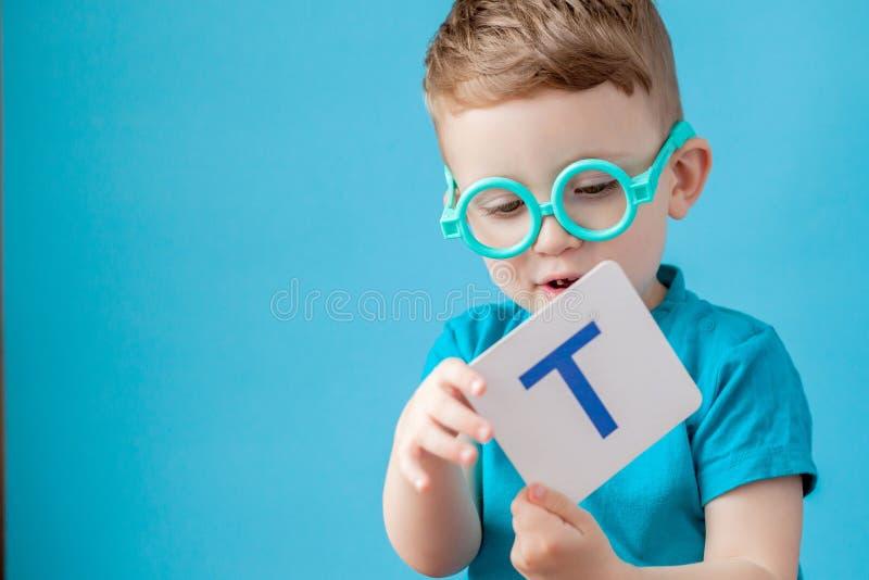 Petit garçon mignon avec une lettre sur fond Lettres d'apprentissage pour enfants Alphabet images libres de droits