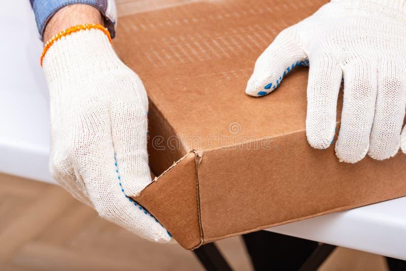 E r Arbetaren öppnar asken med möblemang royaltyfria bilder