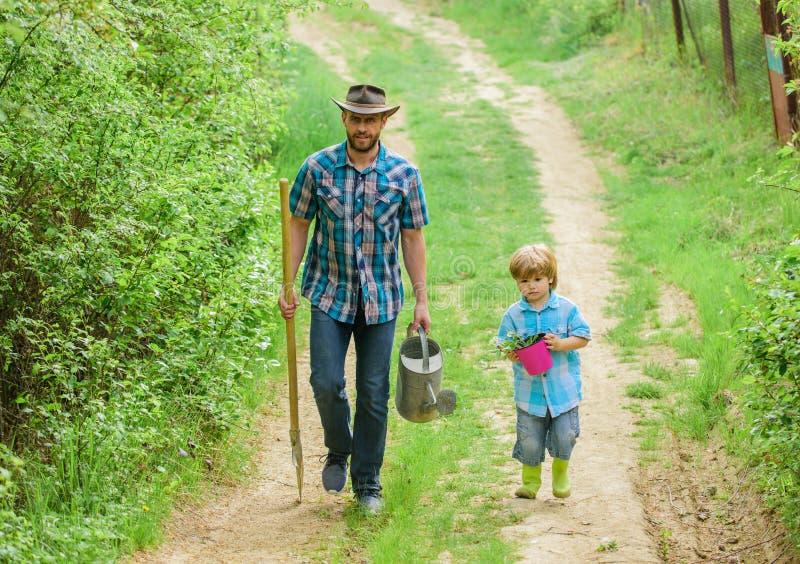 Jongen en vader in de natuur met drenken en schoppen Vader onderwijst zorginstellingen Arbor-dag Aanplantbomen Boom royalty-vrije stock afbeelding