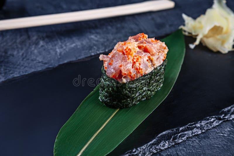 Nära övre sikt på den gunkan sushi med kryddig sås och tonfisk på mörk stenbakgrund Ny japansk kokkonst asiatisk mat Sushibild arkivbilder
