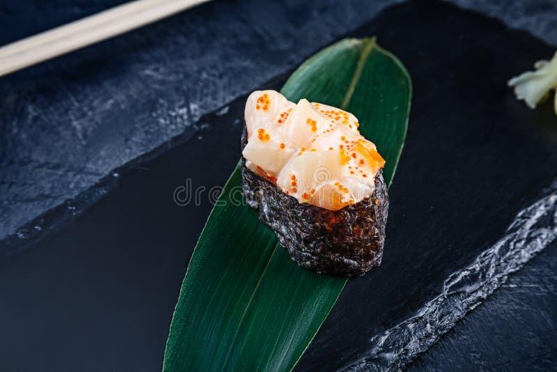 Nära övre sikt på den gunkan sushi med kryddig sås och kammusslan på mörk stenbakgrund Ny japansk kokkonst asiatisk mat Sushi royaltyfria bilder