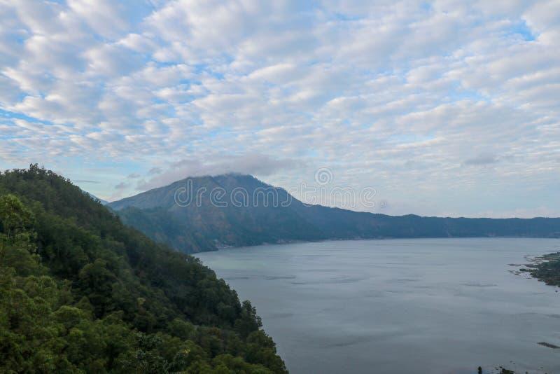 Weergeven achter Batur-vulkaan op caldera met meer en tegenovergestelde Abang-berg Meer met de thermische lentes Bacteries maakt  stock afbeeldingen