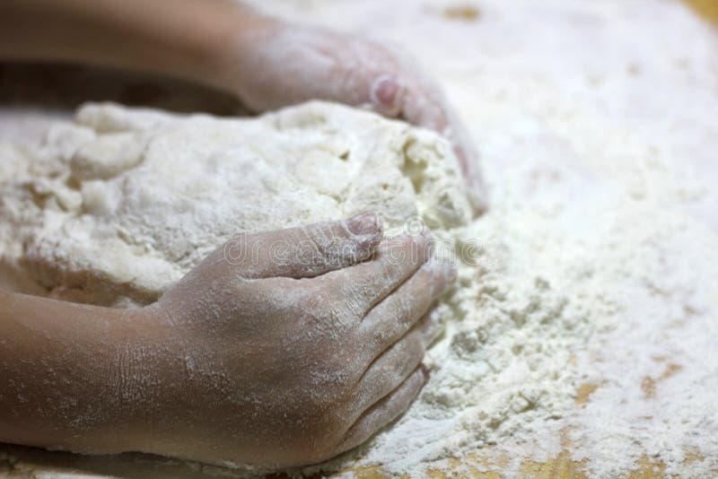 Barns händer och deg En liten pojke som knådar en deg Friska, handgjorda livsmedel bakverk, pizza, mjöl matlagning royaltyfri fotografi