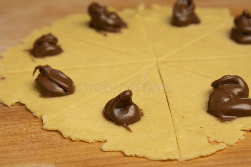 Fabricando rolos de croissant caseiros, puf de pastelaria Croissant de chocolate não cozido Produtos de pastelaria franceses fotografia de stock royalty free