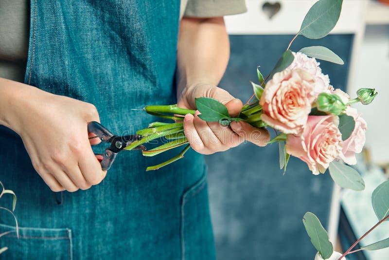 Beskärning av blomsterframställning, färsk bukett Blommor av honkön som står vid räknaren Floral, dekorationsstudio Leverans av b royaltyfri bild