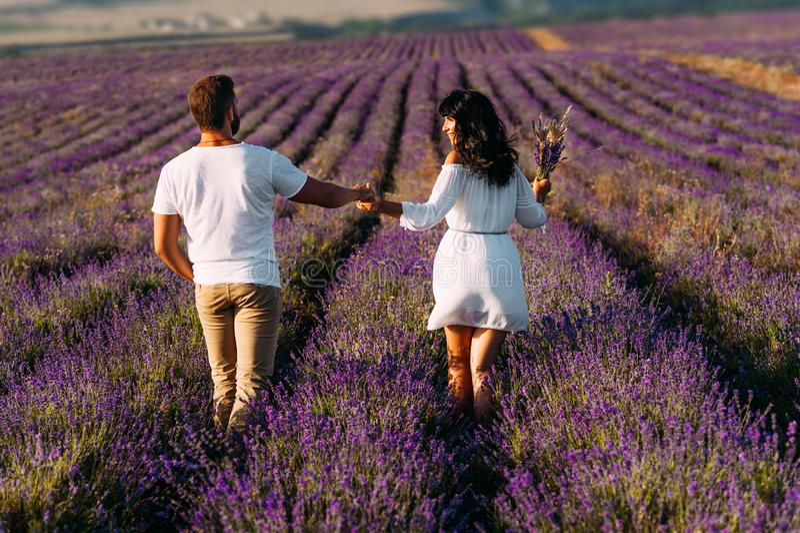 Lyckliga par på lavendelfält Man och kvinna i blommafälten Br?llopsresatur Paret reser världen Lavendel?ngar arkivfoto