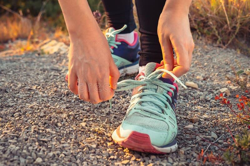 Cordones que intentan de la mujer en las zapatillas de deporte El concepto de forma de vida y de entrenamiento de los deportes Ci imagen de archivo libre de regalías