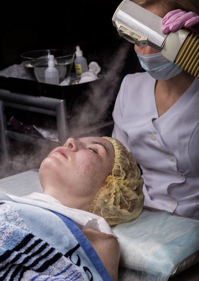 O médico limpa a pele da mulher com um vapor jovem mulher com problemas de pele no belicista Conceito de cosmetologia imagens de stock