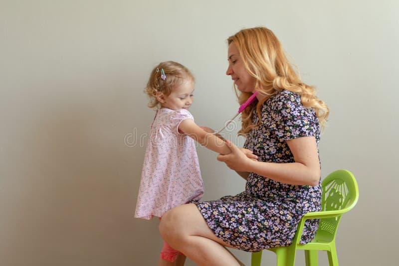 Fille blonde de mère et de petite fille jouant le docteur Planification de succès et protéger les chers Concept d'assurance-malad photographie stock