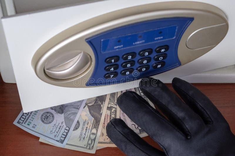 La mano destra con il guanto nero prende soldi dalla porta aperta della cassetta di sicurezza Furto di dollari dalla cassaforte C fotografia stock libera da diritti
