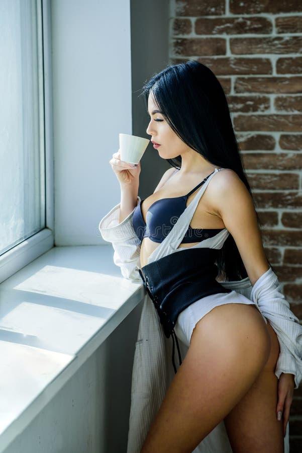 Beber e impulsar su energía Muchacha adorable con curvas sensuales sosteniendo una taza de bebida de cerámica Mujer linda bebiend imágenes de archivo libres de regalías
