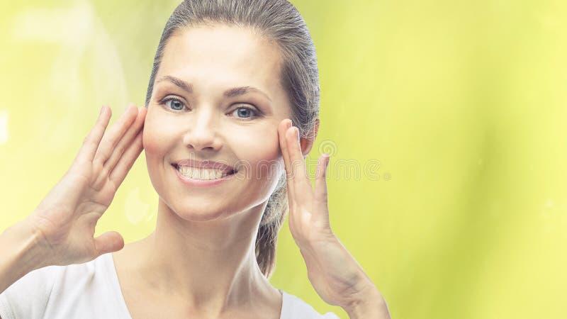 Retrato de belleza natural con manos Cara adulta de cosmetología Crema cosmética Cuidado de la piel Chica elegante fotos de archivo