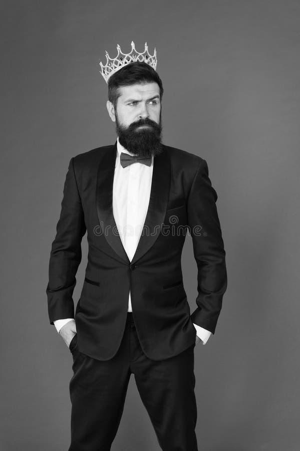 Rey narcisista Hombre barbudo en tuxedo símbolo de la corona dorada de la monarquía Ceremonia del Rey Atributo King Sensación fotografía de archivo libre de regalías