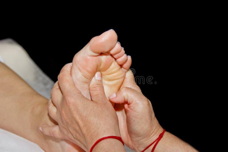 Masaje terapéutico profesional del pie El doctor de la mujer da masajes al atleta en un cuarto del masaje Cuerpo y atenci?n sanit fotos de archivo