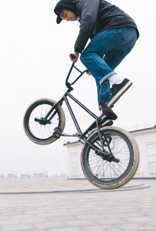 Cierre de BMX freestyle un joven hace acrobacias en una bicicleta BMX Cultura callejera imagenes de archivo