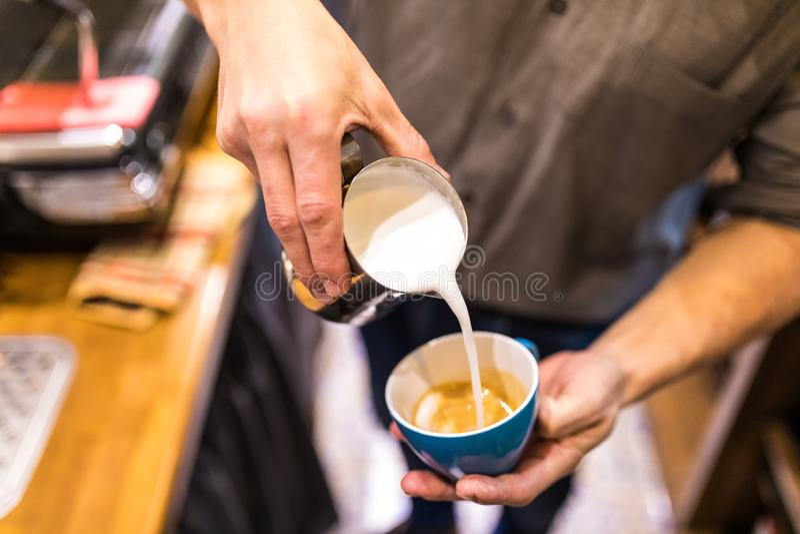 Händchenenge, die Milch gießen und frisches Cappuccino zubereiten Konzept des Kaffeekünstlers und der Zubereitung Morgenkaffee lizenzfreies stockbild