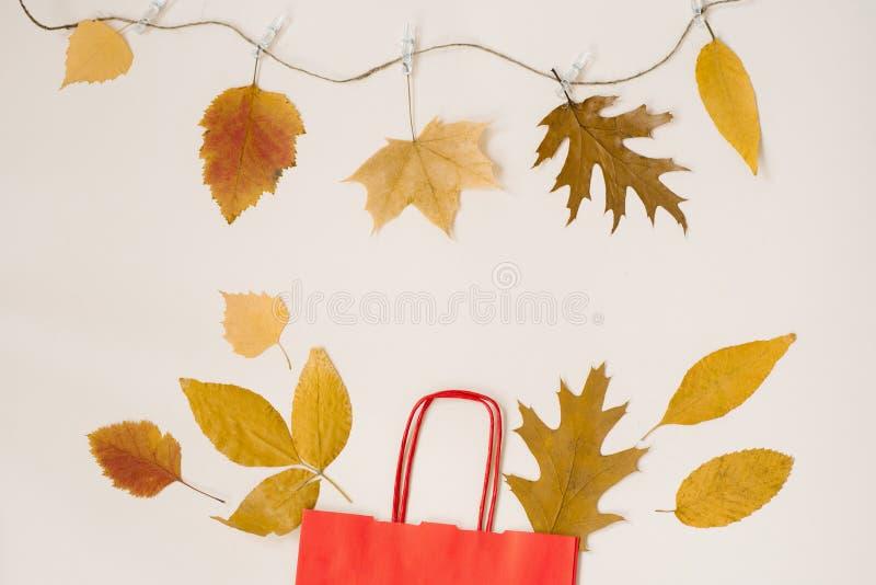 De herfst die met kortingen winkelen Een rode document het winkelen zak met de herfst gele bladeren die uit het gluren De ruimte  royalty-vrije stock fotografie