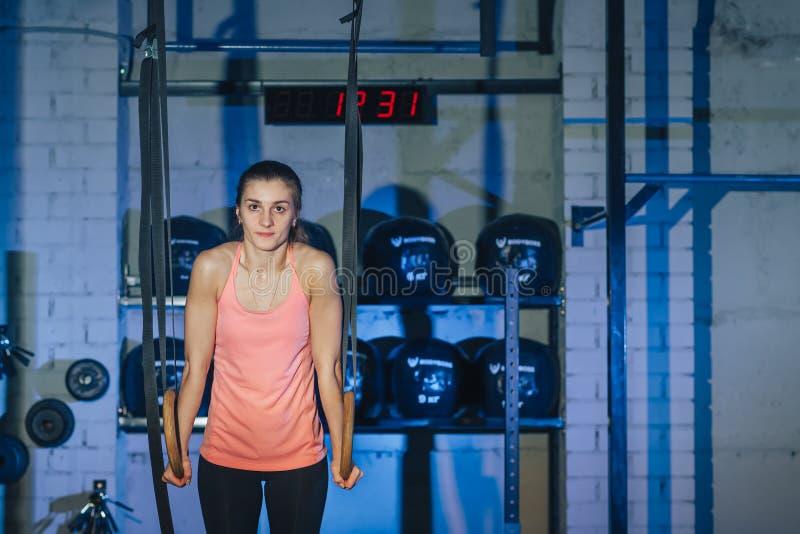 Werkzaamheden aan kruisringen Fitness-vrouw werkt op de TRX in de gym Fitness-vrouw werkt aan het CrossFit Geschiktheid royalty-vrije stock afbeeldingen