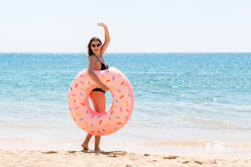 Vrouw roept om in zee te zwemmen en zwaait haar hand Meisje met donut op het strand en spelen met opblaasbare ring zomer royalty-vrije stock afbeelding