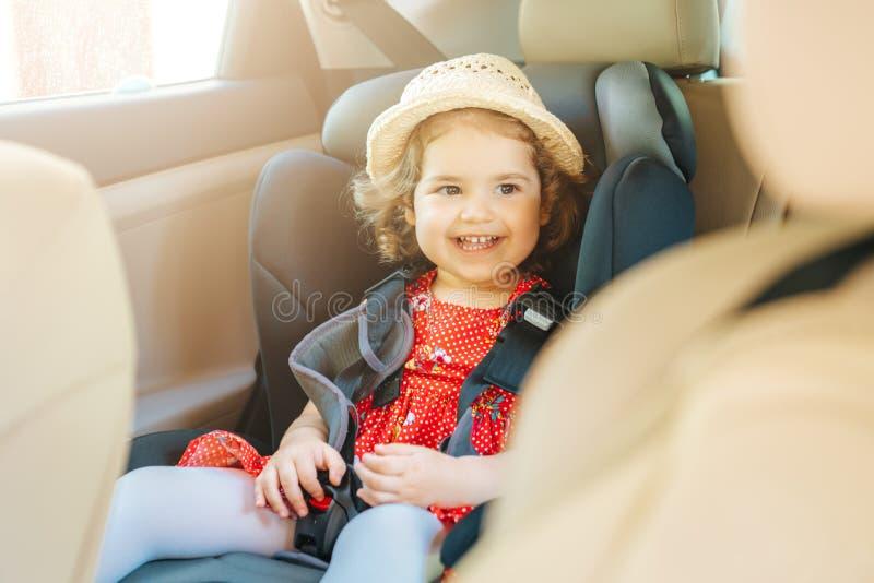 Söt litet spädbarn som sitter i bilstolen Porträtt av söt småbarn som sitter i bilstol Säkerhetskoncept arkivbild