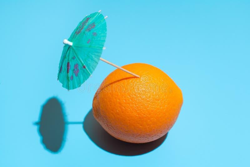 Verse sinaasappel met een cocktailparaplu geïsoleerd op blauwe achtergrond Begrip gezond eten en eten Drinkconcept royalty-vrije stock afbeelding