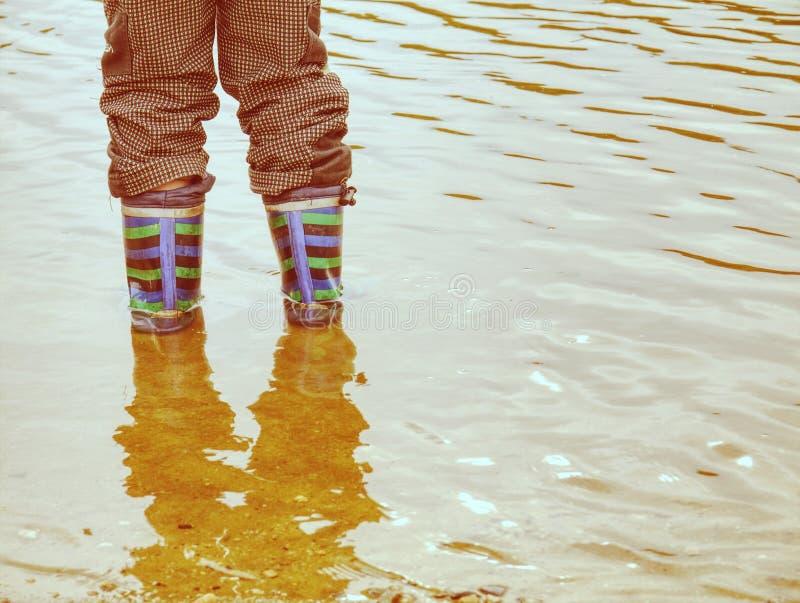 Rzeka Floody Brunatna woda z rzeki Dziecko w gumowych butach obraz stock