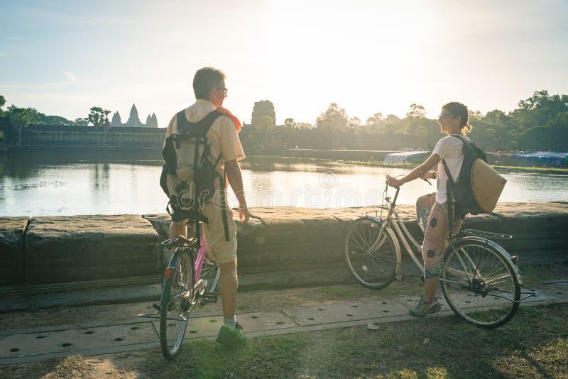 柬埔寨吴哥庙骑自行车的一对旅友 水塘反映吴哥窟主立面 生态旅游 免版税图库摄影