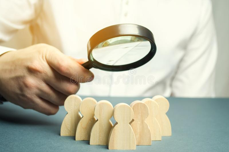 Líder empresarial segurando uma lupa sobre uma equipe de trabalhadores O conceito de encontrar novos empregados Formação de equip fotografia de stock