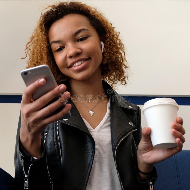 Uma jovem africana bonita está segurando um telefone e uma xícara de café Fone de ouvido sem fios no ouvido Escuta fotos de stock