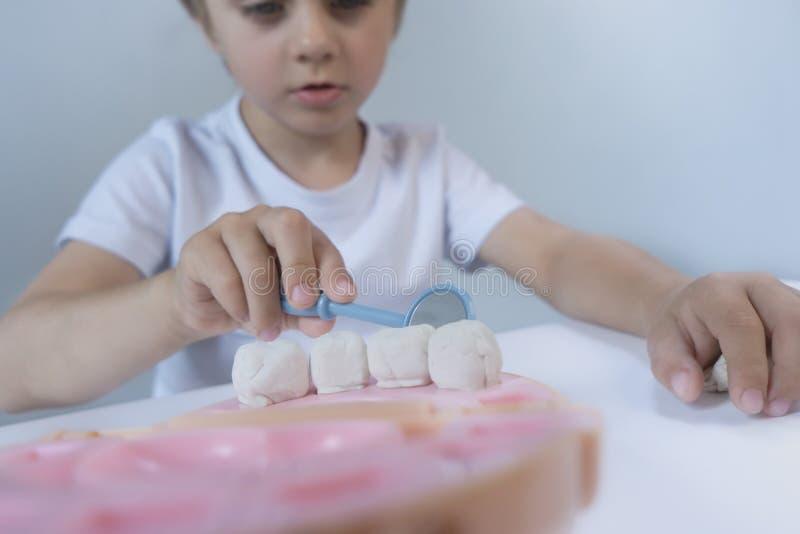Pequeño chico lindo jugando con plasticina de muchos colores Niño jugando con juguetes Herramientas dentales Expresión facial Niñ foto de archivo