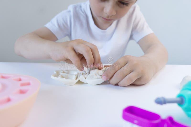 Pequeño chico lindo jugando con plasticina de muchos colores Niño jugando con juguetes Herramientas dentales Expresión facial Niñ fotos de archivo libres de regalías