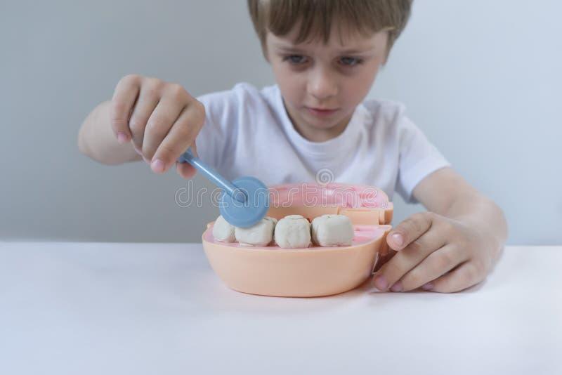 Pequeño chico lindo jugando con plasticina de muchos colores Niño jugando con juguetes Herramientas dentales Expresión facial Niñ fotografía de archivo libre de regalías