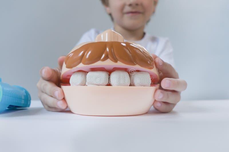 Pequeño chico lindo jugando con plasticina de muchos colores Niño jugando con juguetes Herramientas dentales Expresión facial Niñ imágenes de archivo libres de regalías