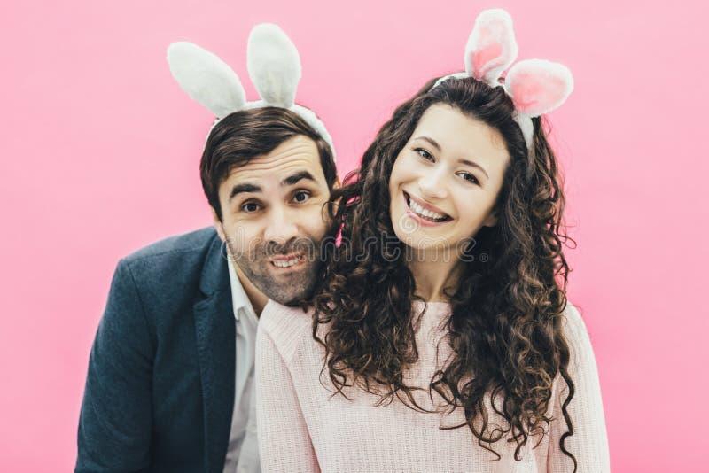 Ung familj på rosa bakgrund Easter Happy-par Semester Ett litet öra Människor från kaninöron Gör dig av med royaltyfria bilder