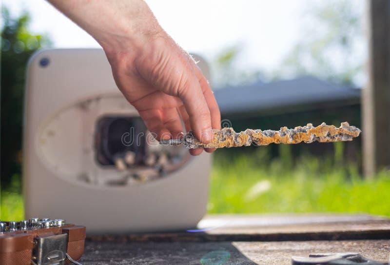 Homem segurando um anodo danificado pela corrosão Em segundo plano, a caldeira com instrumentos e uma vista do gramado Fechar fotos de stock