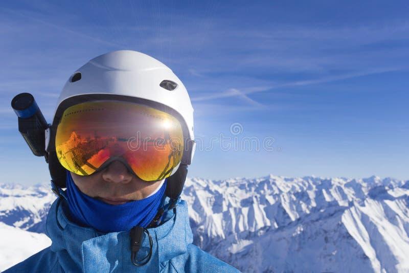 Uomo felice in vetri arancio dello sci sulla cima in montagne delle alpi Su fondo delle montagne Fine in su Natura di inverno fotografia stock libera da diritti
