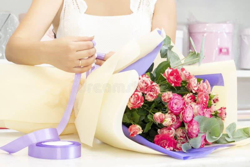 工作在花店的卖花人女孩 新鲜的春天花软的树荫,包裹在装饰纸 Floristry?? 免版税图库摄影
