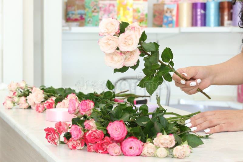 工作在花店的卖花人女孩 新鲜的春天花软的树荫,包裹在装饰纸 Floristry?? 库存照片