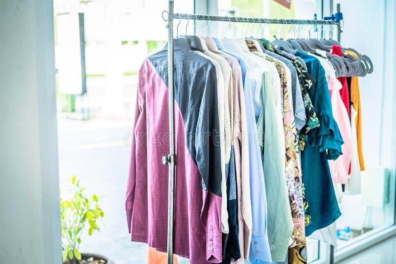 Escaparate de la ropa de verano Géneros de punto blancos y grises del tono que cuelgan en un estante de la capa Foco selectivo, h imagen de archivo libre de regalías