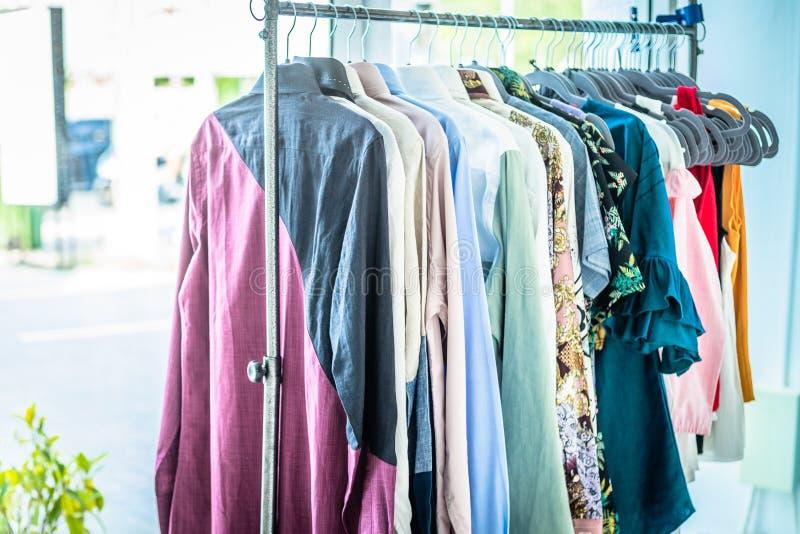 Escaparate de la ropa de verano Géneros de punto blancos y grises del tono que cuelgan en un estante de la capa Foco selectivo, h imagen de archivo