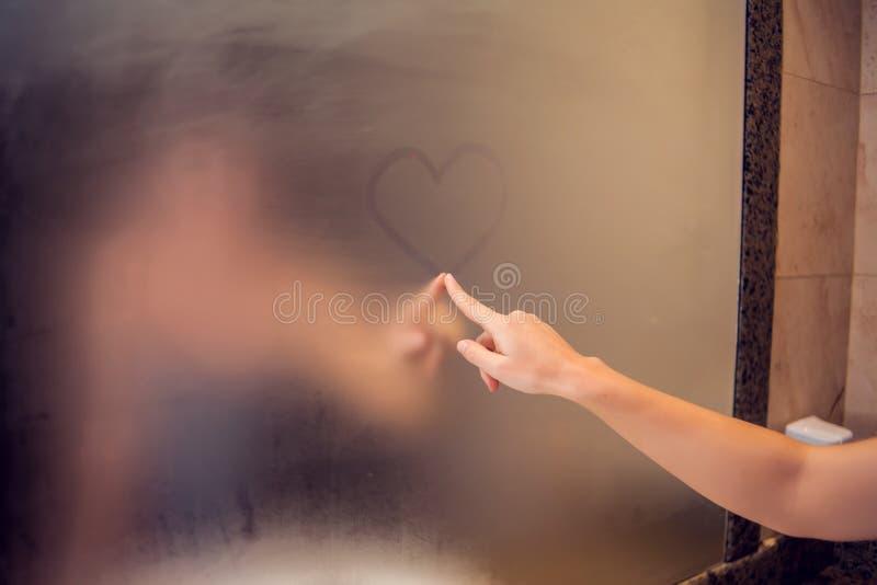 En kvinna drar en hjärta i spegeln Hjärtan identifieras med fingeravtryck på exponeringsglaset i badrum Folk begrepp arkivfoto