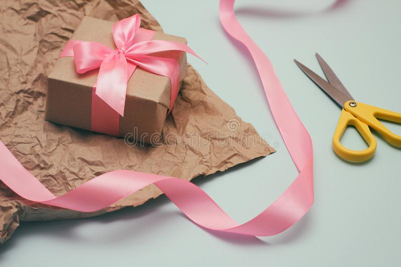 Proceso del embalaje de regalos Papel decorativo, cintas de seda, cajas de regalo, tijeras Fondo azul claro imagenes de archivo
