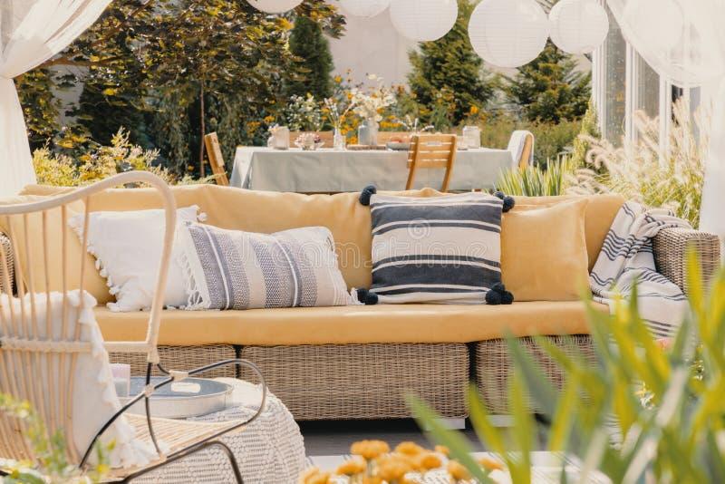 almohadas con motivos en un sofá de mimbre en un jardín Cierre borroso de una planta Foto real foto de archivo libre de regalías